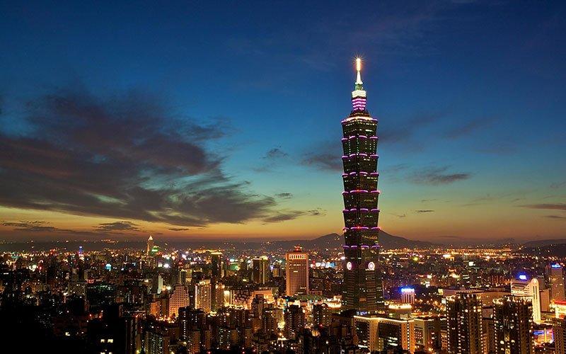 برجی بلند با نورپردازی زردرنگ در بالای آن در تاریکی شب