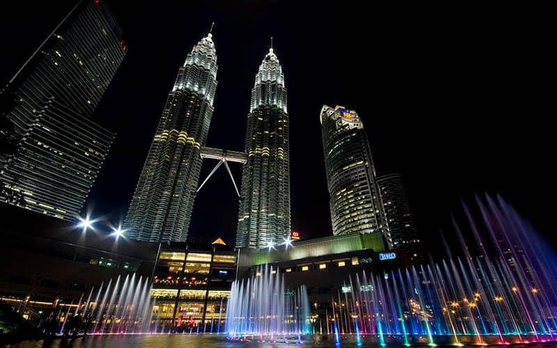 برج های دو قلوی در کنار فواره های آب در شب