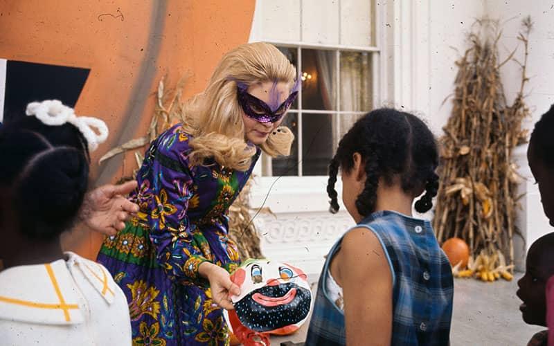 زن جوانی در حال دادن هدیه به کودکان در هالووین