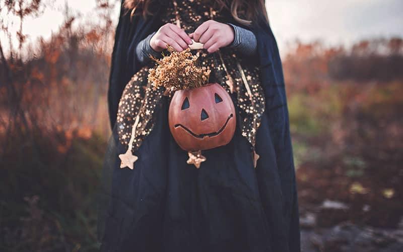 زنی با شنل سیاه و کدوتنبل هالووین در دست