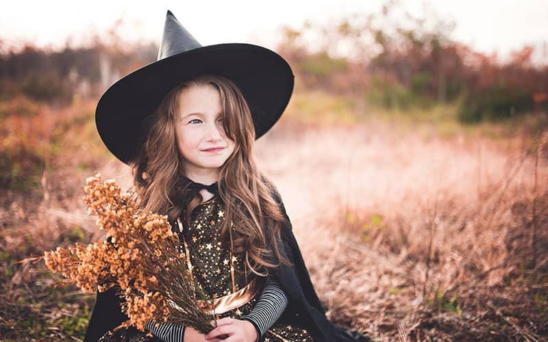 دختربچه ای با کلاه جادوگری و دسته گلی خشکیده در دست