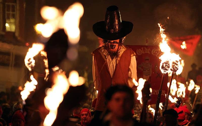 فردی با کلاه در میان مردانی که مشعل به دست دارند