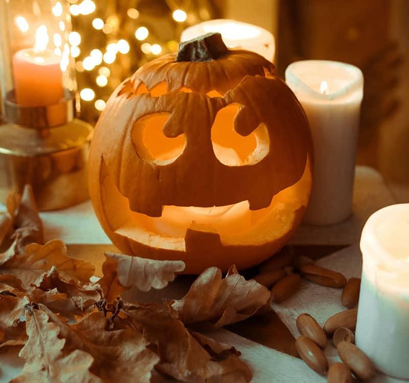کدوی هالووین در کنار چند شمع روشن