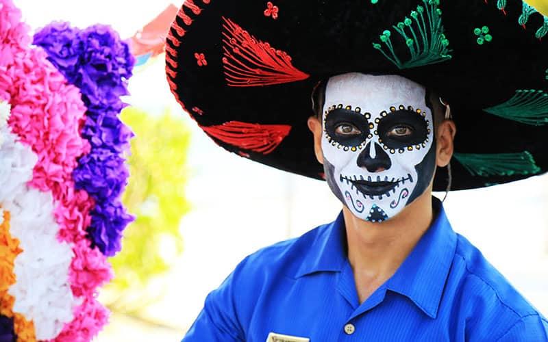 مرد جوانی با صورت نقاشی شده و کلاه مکزیکی